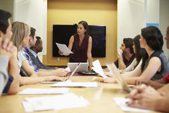 Female Boss Addressing Meeting Around Boardroom Table stock images