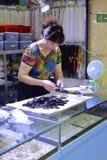 Female boss finishing black gem amulet in liwan jade jewelry market Royalty Free Stock Image