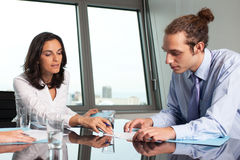 Female boss helping an intern. Female hispanic boss explaining documents to an intern Stock Images