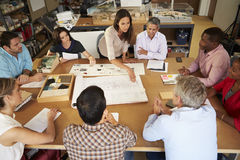 Female Boss Leading Meeting Of Architects Sitting At Table Stock Image
