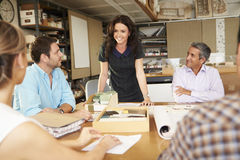 Female Boss Leading Meeting Of Architects Sitting At Table. Smiling At Colleagues Royalty Free Stock Image