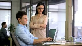 Female boss and male employee looking laptop, working on business project office stock photo