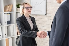 Female Boss Shaking Hands with Partner Stock Photo