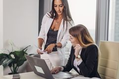 Female boss showing documents to personal assistant giving instructions and tasks.  royalty free stock image