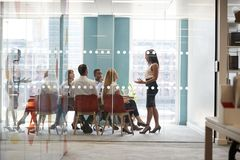 Female boss stands addressing colleagues at business meeting royalty free stock photo
