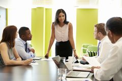 Female boss stands addressing team at informal work meeting stock photography