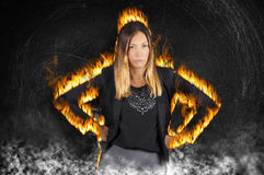 Female boss woman burning with rage. Very angry with fire flames and smoke. A fiery woman has her fists on her hips with an aggressive attitude. Black painted Stock Photo