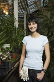 Female Botanist Standing In Greenhouse. Portrait of young female botanist standing in greenhouse Royalty Free Stock Images