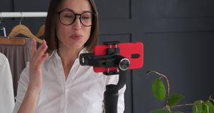 Fashion designer using mobile phone handheld gimbal for new outfit vlogging. Female boutique owner using mobile phone handheld gimbal for new outfit vlogging stock video footage