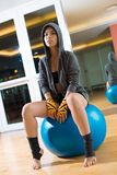 Female boxer. Vertical portrait of a female boxer in hoodie sitting on a gym ball Stock Photos