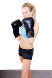 Female Boxer. Young female boxer in black boxing gloves in the gym training for a fight Royalty Free Stock Photo