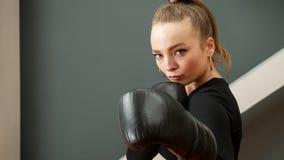 Female boxer in black gloves