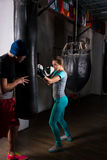 Female boxer in boxing gloves training with her trainer and boxi Stock Images
