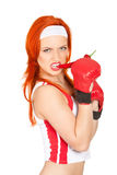 Female boxer with chili pepper. Portrait of pretty and angry female boxer biting hot chili pepper Royalty Free Stock Photo