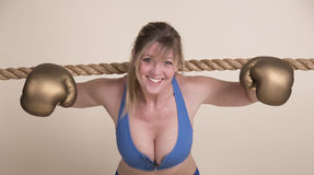 Female boxer coming under the ropes Royalty Free Stock Photos