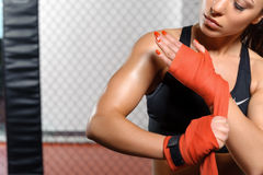 Female boxer does bandage. Cruel beauty. Female boxer binding boxing gloves and preparing for training Royalty Free Stock Photography