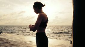 Female boxer getting her fists ready for the boxing gloves by wrapping bandage around them standing against the sun. Young woman wrapping hands with boxing stock footage