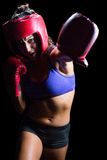 Female boxer with gloves and headgear punching Royalty Free Stock Photo