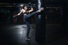 Female boxer hitting a huge punching bag at a boxing studio. Wom royalty free stock photography