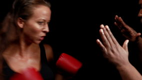 Female boxer hitting on trainer hand. On black background stock video footage