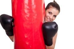 Female boxer holding punching bag Stock Images