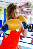 Female boxer inside thai boxing ring. angree emotions. Close up of a female boxer inside a boxing ring. Woman boxer at a boxing studio Royalty Free Stock Photography