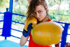 Female boxer inside thai boxing ring. angree emotions. Close up of a female boxer inside a boxing ring. Woman boxer at a boxing studio Stock Image
