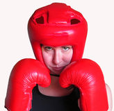 Woman boxer isolated. Fighting. A female boxer wearing red boxing gloves and head-guard ready to fight. Isolated on white. Fighting woman Stock Photos