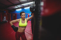Female boxer leaning on punching bag Royalty Free Stock Photos