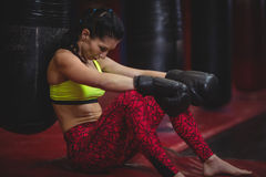 Female boxer leaning on punching bag Royalty Free Stock Photography