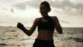 Female boxer makes side kick of her legs against the sun by the sea in slow motion. Beautiful female boxer training on. The beach in the morning, throwing stock video footage