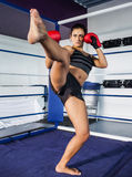 Female boxer performing an air kick in the ring Stock Photo