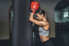 Female boxer with punching bag Royalty Free Stock Images