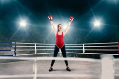 Female boxer in red sportswear hands up on ring stock images