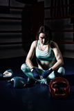 Female boxer sitting near lying boxing gloves and helmet Royalty Free Stock Photography