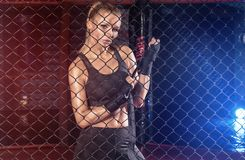 Female boxer posing inside a boxing cage. Female boxer standing inside a boxing cage. Attractive blonde woman with perfect fit body Royalty Free Stock Photography