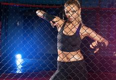 Female boxer posing inside a boxing cage. Female boxer standing inside a boxing cage. Attractive blonde woman with perfect fit body Stock Photo