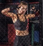 Female boxer posing inside a boxing cage. Female boxer standing inside a boxing cage. Attractive blonde woman with perfect fit body Royalty Free Stock Images