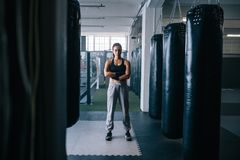 Female boxer at the boxing studio. Female boxer standing inside a boxing studio with her hands folded. Woman standing in a boxing training centre with punching Stock Photos