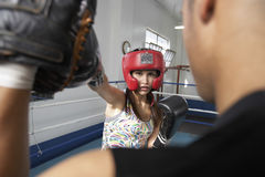 Female Boxer Striking Her Target In Ring. Portrait of young female boxer striking her target in ring stock photos