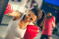 Female Boxer At Training. Attractive Female Punching A Bag With Boxing Gloves On Stock Photo