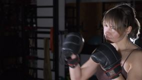 Female Boxer training in Boxing Club. The sports beautiful woman beats a punching bag. The woman in the gym. The trainer stock footage