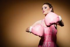 Female boxer wearing big fun pink gloves playing sports Royalty Free Stock Image