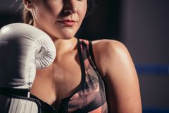 Female Boxer wearing gloves posing in boxing studio. Close up of woman boxer wearing gloves standing in boxing studio Stock Photos