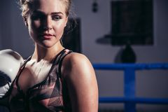 Female Boxer wearing gloves posing in boxing studio. Close up of woman boxer wearing gloves standing in boxing studio Royalty Free Stock Photo