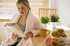 Female with breakfast and newspaper in kitchen Stock Images