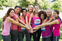 Female breast cancer marathon runners stacking hands Royalty Free Stock Image