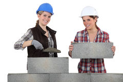 Female bricklayers. Building a stone wall Royalty Free Stock Images