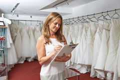 Female Bridal Store Owner With Wedding Dresses Royalty Free Stock Photography