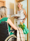 Female bringing food to invalid Stock Photo